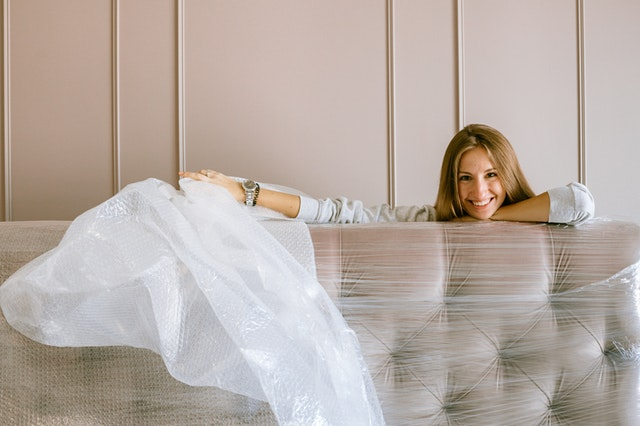 a woman unpacking her mattress and smiling
