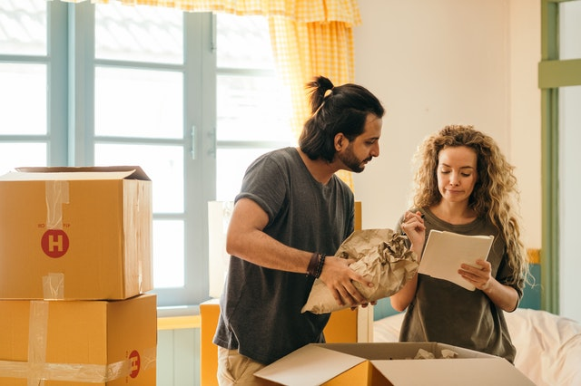 a man and a woman packing their things with the help of a list