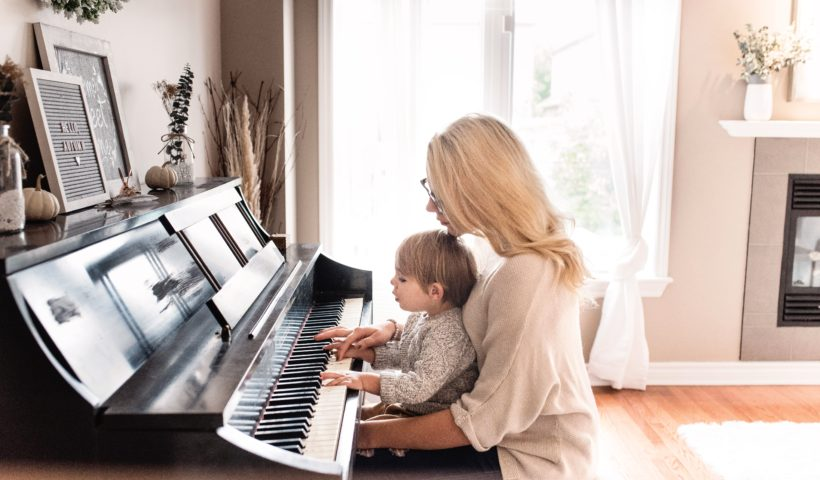 Woman playing piano with her chind in her lap